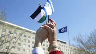 Hands join to hold together the flags of Israel and Palestine. For the AU or South Africa to play a meaningful in helping to broker peace between Israel and the Palestinians, perhaps more co-operation and listening is needed and less recrimination, says the writer. File picture: Kevin Lamarque/Reuters
