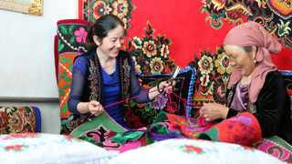 Hanipa Nabi, a villager from Altay, northwest China's Xinjiang Uygur autonomous region has joined embroidery sessions offered by a local foreign trade company, makes embroidery works at home. (Photo by Aldak/People's Daily Online)