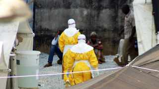 Health workers wearing protective suits enter an isolation centre for people infected with Ebola at Donka Hospital in Conakry. Picture: Cellou Binani