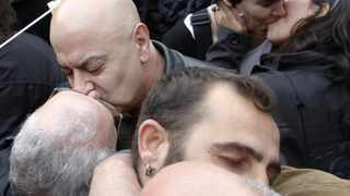 Homosexual couples kiss in the Plaza de la Catedral as the Pope travels in his Popemobile to the Sagrada Familia temple in Barcelona.