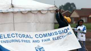 IEC officials erect a banner at a voting station in the troubled township of Khutsong on the West Rand. Picture: Werner Beukes/SAPA
