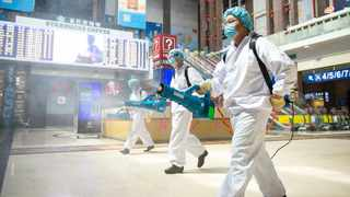 In this June 18, 2020, photo released by China's Xinhua News Agency, workers spray disinfectant in the central hall of the Beijing Railway Station in Beijing. New confirmed cases of coronavirus remained stable in China's capital on Friday after a public health official declared Beijing's latest outbreak under control. (Chen Zhonghao/Xinhua via AP)