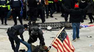 In this file photo taken on January 6, 2021, police detain a person as supporters of US President Donald Trump riot outside the US Capitol in Washington, DC. Picture: ROBERTO SCHMIDT / AFP)