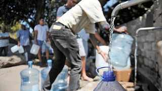 In this file picture, residents from a drought stricken area in Cape Town are seen queuing and waiting their turn to fill their water bottles.