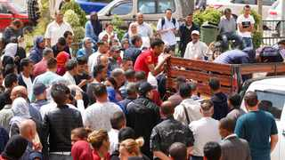 In this photo dated Monday, June 4, 2018, people wait to receive the bodies of loved ones after the sinking of a boat carrying migrants the previous day, in the coastal city of Sfax, Tunisia. Tunisia's interior minister has fired 10 security officials amid an investigation into the sinking of a boat carrying migrants trying to reach Europe that left an estimated 112 dead or missing. (AP Photo)