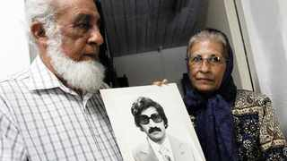Ishmail Haffejee and Sara Lall with a photograph of their brother, Hoosen Haffejee, who died while in police detention in 1977.