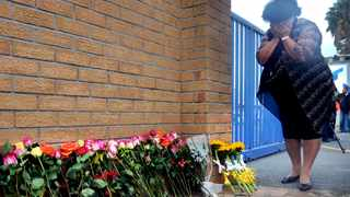 Jacoba Mouton puts flowers in front of the gate at Rheinmetall Denel Munition factory following the deadly blast. File picture: Ayanda Ndamane/African News Agency/ ANA