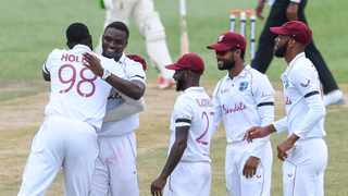 Jayden Seales (2nd L), Jermaine Blackwood (3rd R), Shai Hope (2nd R) and Roston Chase (R) of the West Indies celebrate the dismissal of Keegan Petersen of South Africa during day one of the second Test at Darren Sammy Cricket Ground on Friday. Photo: Randy Brooks/AFP