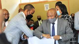 """KwaZulu-Natal premier Sihle Zikalala does the new """"elbow shake"""" with the principal of Nhlanhlayetu Secondary in Inanda after monitoring their state of readiness to operate safely amid the coronavirus pandemic. Image: Jehran Daniel / African News Agency (ANA)"""