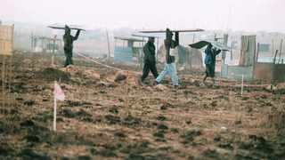 Land invaders carrying corrugated iron sheets which they will use to build structures on land illegal acquired. File Picture: TJ Lemon