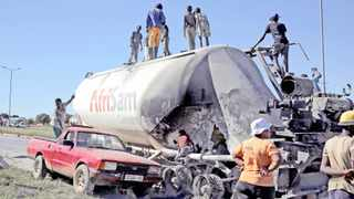 Locals loot cement from an AfriSam cement truck during protests in Mahikeng, North West Province. Picture: Siphiwe Sibeko/Reuters