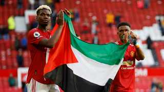 Manchester United's Paul Pogba and Amad Diallo applaud fans while holding a Palestinian flag during a lap of appreciation after their Premier League match against Fulham at Old Trafford on Tuesday. Photo: Phil Noble/Reuters