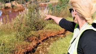 Mariette Liefferink points out a lake that still shows the effect of treated water at the acid mine drainage plant near Krugersdorp say much need to be done to really get the problem under control. Picture: Timothy Bernard/African News Agency/ANA