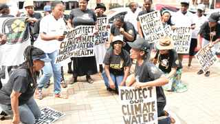 Members of the environmental and anti-nuclear organisation, Earthlife Africa, sing and chant outside the high court in the city. Picture: Thobile Mathonsi