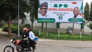 Men ride a motorbike past a sign for the All Progressive Congress (APC) national headquarters in Abuja. Nigeria's biggest city has partially banned the use of motorcycle taxis following an escalating number of fatal accidents.