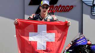 Monster Energy Yamaha MotoGP's Fabio Quartararo holds a Switzerland flag after winning the race as a tribute to Moto3 rider Jason Dupasquier who died from injuries sustained in Saturday's qualifying. Photo: Ciro De Luca/Reuters