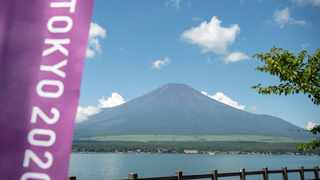 Mount Fuji, Japan's highest mountain at 3,776 meters (12,388 feet), seen from Lake Yamanaka, next to a Tokyo 2020 Olympics banner. Photo: Charly Triballeau/AFP