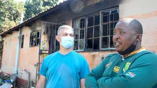 Neighbours Beltsazer van der Merwe and Tshepo Meremi outside the burnt Neething home in Danville. Picture: Jacques Naude/African News Agency(ANA)