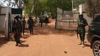 Nigerian soldiers and police officers stand at the entrance of the Federal College of Forestry Mechanisation in Mando, Kaduna state, after a kidnap gang stormed the school, shooting indiscriminately before taking at least 30 students on March 11, 2021. Picture: Bosan Yakusak / AFP
