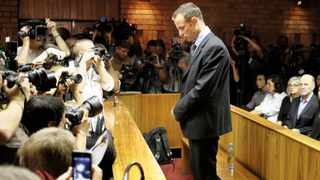 Oscar Pistorius stands surrounded by photographers during his bail application at Pretoria Magistrates Court.