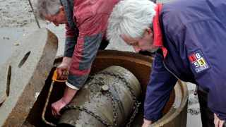 Oyster farmer Joel Dupuch and general director of wine producers Chateau Larrivet Haut-Brion, Bruno Lemoine recover a wine barrel.