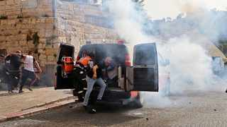 Palestinian medics evacuate wounded protesters as Israeli security forces fire tear gas in Jerusalem's Old City. Picture: Emmanuel Dunand/AFP
