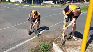 Panorama Residents' Association got together with members of the community to fill potholes as well as removing weeds and trees growing between pavement stones and stormwater drains. Picture: Facebook.