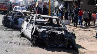 Pedestrians pass burnt out cars on the side of a street on the outskirts of Johannesburg. Picture: AP Photo