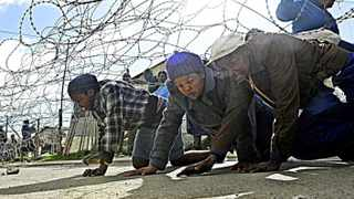 People crawl under a roll of barbed wire during the evictions in Lwandle in June. File picture: Cindy Waxa