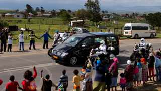 People hold hands as the hearse carrying the remains of former South African President Nelson Mandela proceeds to Mandela's hometown and burial site in Qunu, South Africa, Saturday Dec. 14, 2013. The iconic leader will be buried on Sunday close to his house. (AP Photo/Peter Dejong)