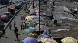 People shop at a roadside market with few customers in Lagos, Nigeria. Picture: Sunday Alamba/AP