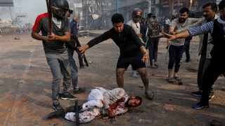 People supporting the new citizenship law beat a Muslim man during a clash with those opposing the law, in New Delhi, India. File picture: Danish Siddiqui/Reuters
