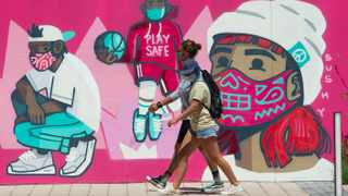 People walking past a mural of kids playing with their face masks at the V&A Waterfront in Cape Town. Picture: Henk Kruger/African News Agency(ANA)