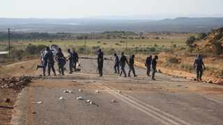 Police clear the R52 road between Koster and Rustenburg during a violent service delivery in Koster in May. PHOTO: ANA Reporter