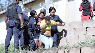 Police manhandle a pair of women who resisted the eviction of tenants from units at the Howell Road housing development in Sydenham yesterday, while a member of the Red Ants, right, looks on. Picture: Sibusiso Ndlovu