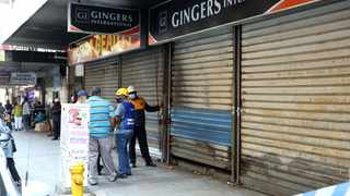 Police prepare to enter a burnt out store in Durban's Monty Naicker Street where three charred bodies were found. Picture: Shelley Kjonstad/African News Agency (ANA)