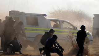 Policemen in teargas and dust open fire on striking miners at the Lonmin Platinum Mine near Rustenburg. Photo: AP