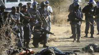 Policemen keep watch over striking miners after they were shot outside a South African mine in Rustenburg, 100 km (62 miles) northwest of Johannesburg, August 16, 2012. South African police opened fire against thousands of striking miners armed with machetes and sticks at Lonmin's Marikana platinum mine, leaving several bloodied corpses lying on the ground.