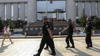 Policemen patrol as a woman walks past in front of a court, where four suspects are on trial in connection with the Kunming railway station attack, in Kunming, Yunnan province. Picture: Wong Campion