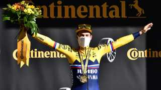 Primoz Roglic of Slovenia celebrates on the podium after claiming the leader's yellow jersey. Photo: Anne-Christine Poujoulat/Reuters