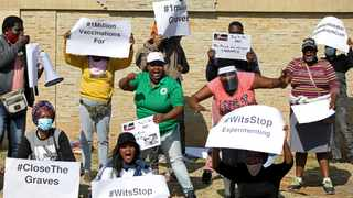 Protesters hold placards during a demonstration against Covid-19 vaccine testing outside Baragwanath hospital in Soweto. Picture: Siphiwe Sibeko/Reuters