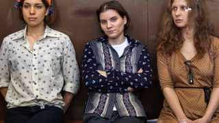Pussy Riot members, from left, Nadezhda Tolokonnikova, Yekaterina Samutsevich and Maria Alekhina sit in a glass cage at a court room in Moscow.