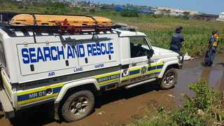 RECOVERED: Police search for a body washed up near the canal during the Durban Storm.