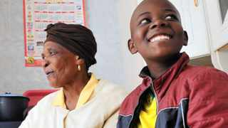 Rebecca Zulu with her grandson, Nkamogelang Baloyi, supervising him while he is doing his homework. She has difficulties helping him as she doesnt understand some of his subjects. Photo: Thobile Mathonsi