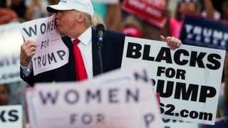 """Republican presidential candidate Donald Trump kisses a """"Women for Trump"""" sign during a campaign rally in Lakeland, Florida. Picture: Evan Vucci"""