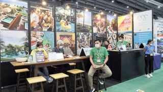 Sales staff from a travel agency wait for customers at a travel expo in Bangkok, Thailand, this week. Picture: EPA-EFE