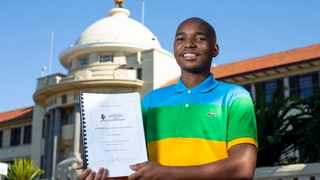 Scelo Manyoni, Master of Development Studies graduate holding up a copy of his thesis on Black Tax and ubuntu at the Howard College Campus. Photographer : Rogan Ward