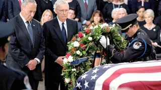 Senator Chuck Schumer, left, and Mitch McConnell watche as a wreath is placed on the casket of Senator John McCain as he lies in state in the Rotunda of the US Capitol in Washington, yesterday. He will be buried today. Andrew Harnik/POOL Via REUTERS