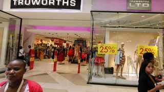 Shoppers walk past a Truworths shop with Sale advertisements on its windows at the Sandton shopping mall in Johannesburg January 30, 2012. REUTERS/Siphiwe Sibeko (SOUTH AFRICA - Tags: FASHION BUSINESS TEXTILE)