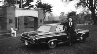 Skonk with his old Chrysler Valiant in about 1990. The arch in the background is the Nicholson Arch – the First XV runs through the arch on its way to the main field, Goldstone's. It was commissioned in 1982, the year of Skonk's retirement.